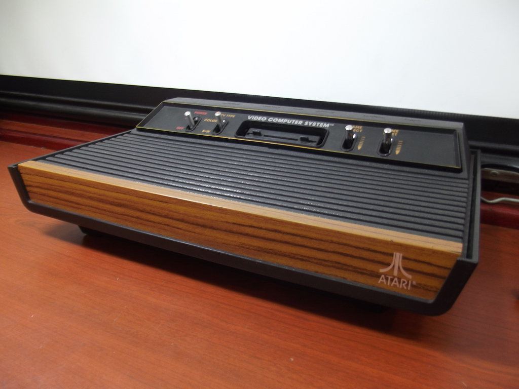 An original Atari 2600 gaming console sits in front of a white screen on a wooden table. It displays the classic