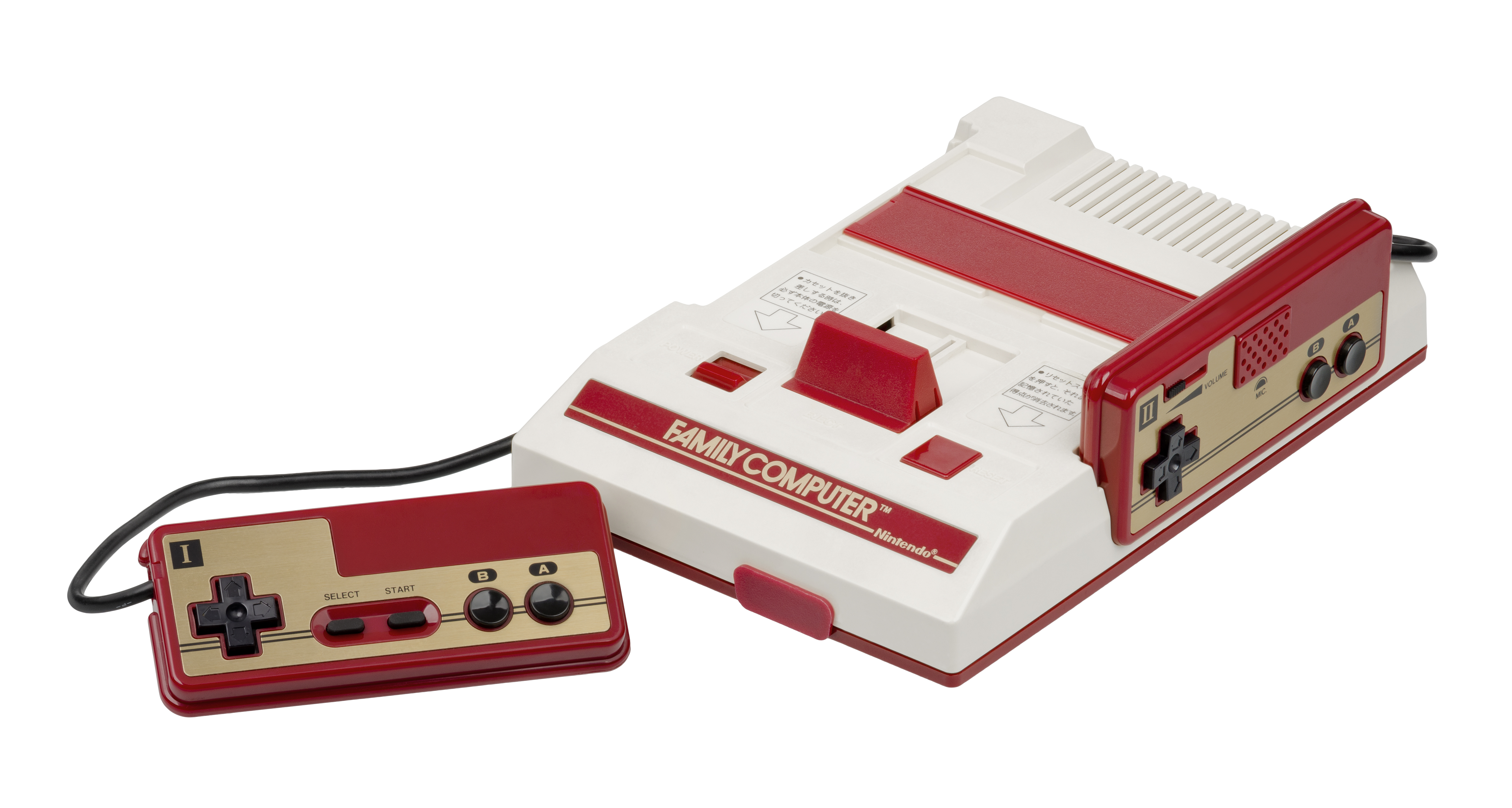 A Nintendo Famicom gaming console sits in a white space. It is a white console with slots on the left and right for controllers to rest when not in use. One controller is facing the screen and is connected to the Famicom by a cable.